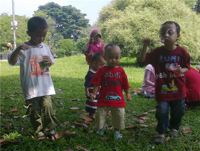 Anak-anak ceria meniup balon di udara
